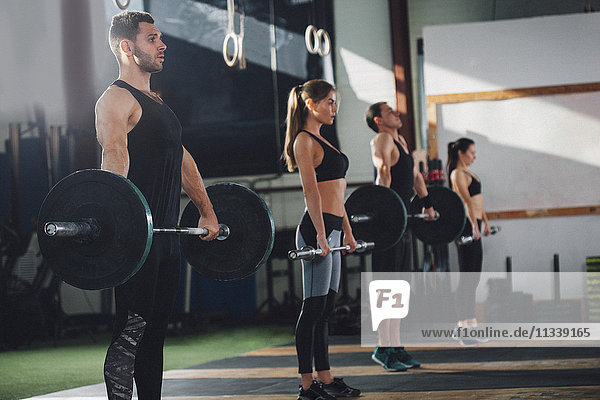 Seitenansicht der Athletinnen und Athleten beim Heben von Hanteln im Fitnessstudio