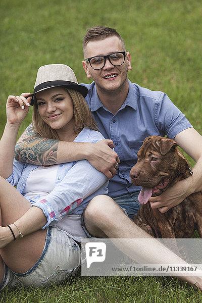 Ein Paar mit ihrem Shar-pei/Staffordshire Terrier Hund im Park