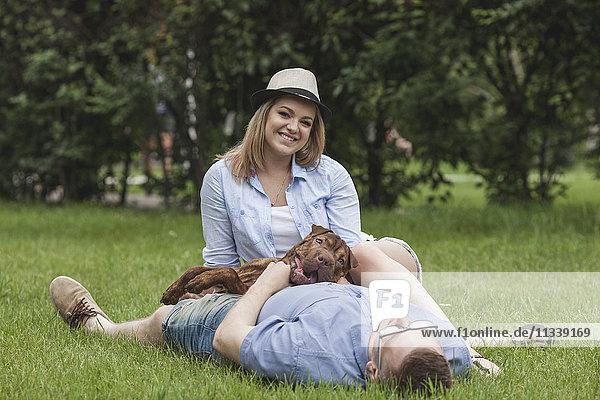Ein Mann  der mit seinem Hund schläft  während seine Freundin sich bei ihm ausruht.