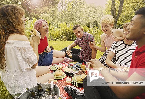 Fröhliche Freunde beim Essen während der Party im Hof