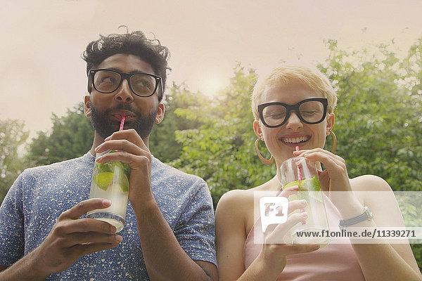 Flachwinkelansicht eines fröhlichen Paares beim Limonadentrinken im Hof