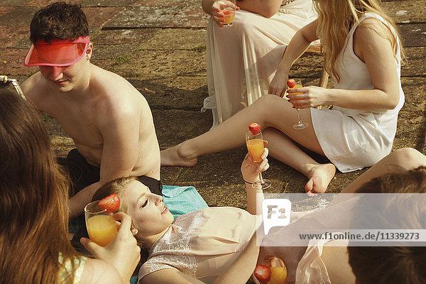 Großer Blickwinkel auf Freunde  die Getränke halten und sich am Pool entspannen.