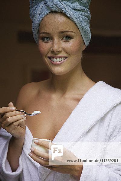 Porträt einer glücklichen jungen Frau im Bademantel  die zu Hause Joghurt isst.