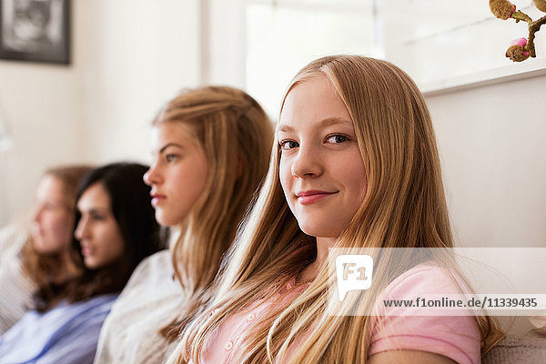 Portrait of confident teenage girl sitting on sofa while friends watching TV at home