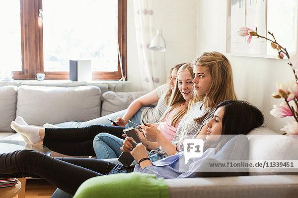 Seitenansicht von Teenagern beim Fernsehen auf dem Sofa zu Hause