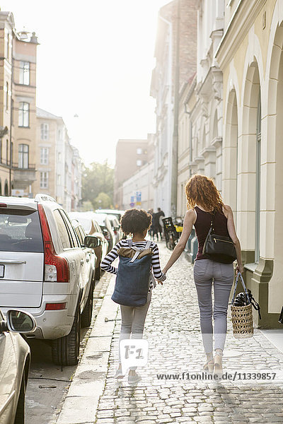 Rear view of woman and daughter walking on sidewalk in city