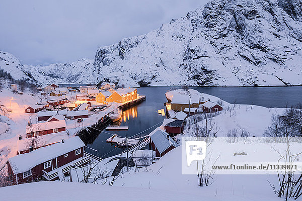 Dusk lights on the fishing village surrounded by snowy peaks  Nusfjord  Nordland  Lofoten Islands  Northern Norway  Scandinavia  Europe