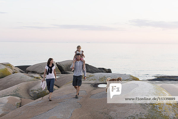 Frau schaut den Mann an  der ein Mädchen auf der Schulter trägt  das gegen den Himmel geht.