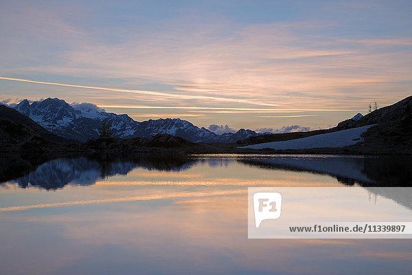 Snowy peaks reflected in Lake Zana at sunrise  Malenco Valley  Valtellina  Province of Sondrio  Lombardy  Italy  Europe