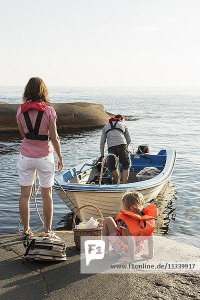 Rückansicht von Frau und Tochter mit Blick auf den Mann auf dem Motorboot bei klarem Himmel