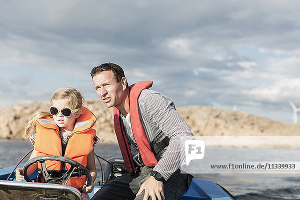 Girl driving motorboat with father in Baltic Sea against sky