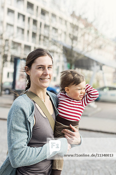 Porträt einer glücklichen Mutter  die ein kleines Mädchen in der Stadt trägt.