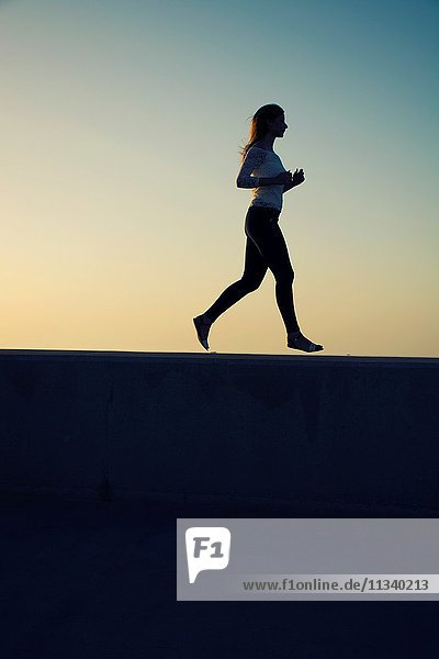 Silhouette of a woman running outdoors.