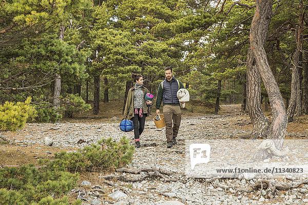Paar mit Schlafsäcken und Korb im Wald