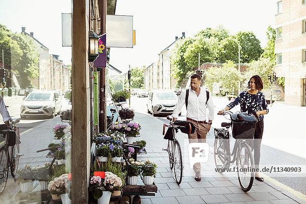 Geschäftsleute mit Fahrrädern auf dem Bürgersteig in der Stadt
