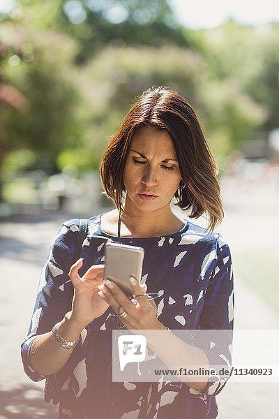 Reife Geschäftsfrau mit Smartphone im Sommer auf dem Fußweg im Park