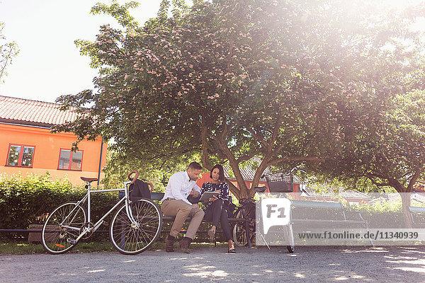 Geschäftsleute  die mit dem Fahrrad auf der Parkbank sitzen und ein digitales Tablett benutzen.