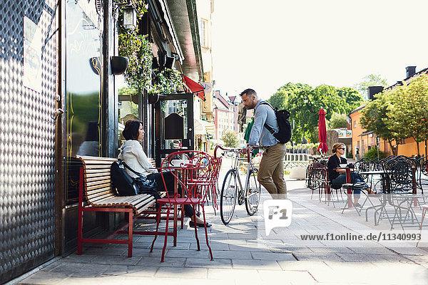 Volle Länge des Geschäftsmannes mit Fahrrad im Gespräch mit Kollegen im Straßencafé