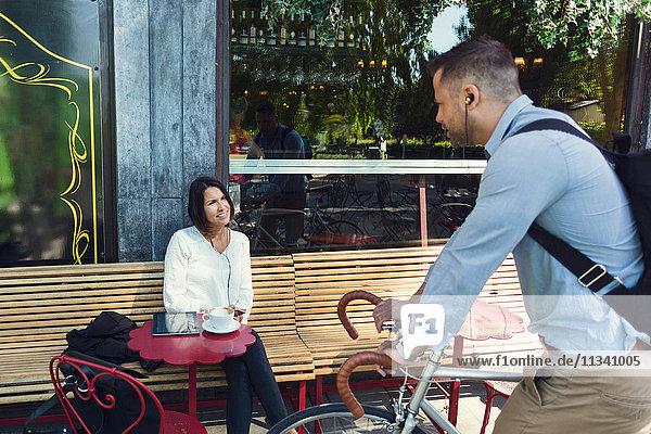 Geschäftsmann mit Fahrrad im Gespräch mit einem Kollegen  der im Straßencafé sitzt.