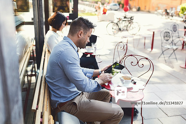 Geschäftsmann mit digitalem Tablett im Straßencafé