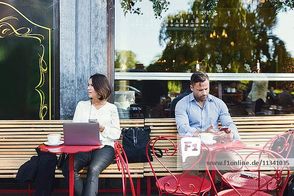 Geschäftsleute  die Technologien im Straßencafé nutzen.
