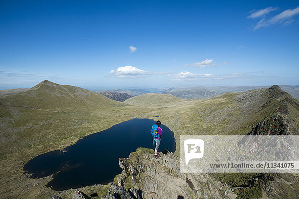 A woman stands on top of Striding Edge with a view of Red Tarn below and Ullswater in the far distance  Lake District National Park  Cumbria  England  United Kingdom  Europe