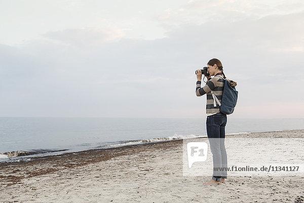 Volle Länge der Frau  die den Rucksack trägt und das Meer gegen den Himmel fotografiert.
