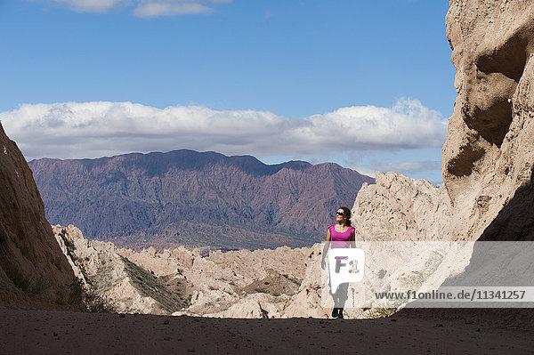 A girl walks through the stunning rock formations of the Quebrada de las Flechas  Argentina  South America