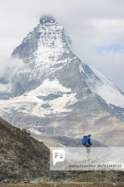 Hiking a trail in the Swiss Alps near Zermatt with a view of The Matterhorn in the distance  Zermatt  Valais  Switzerland  Europe