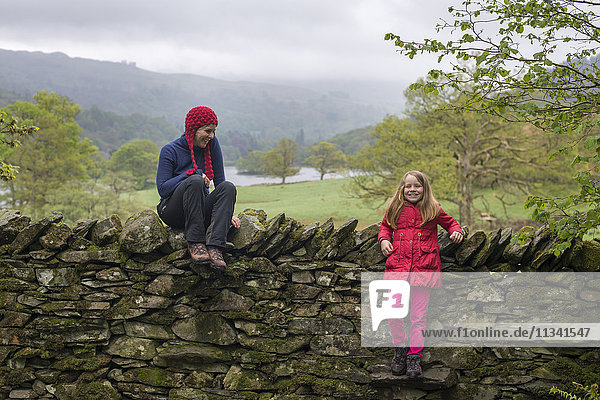 Mother and daughter rest on a dry stone wall while on holiday in the Lake District  Cumbria  England  United Kingdom  Europe