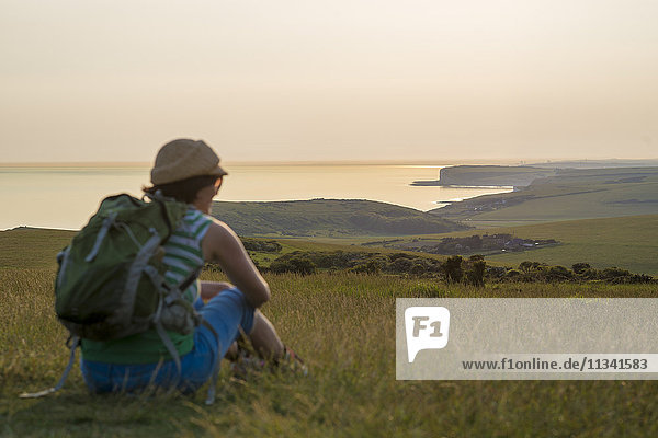 A woman looks out to sea near Beachy Head with views of the Seven Sisters coastline in the distance  South Downs National Park  East Sussex  England  United Kingdom  Europe