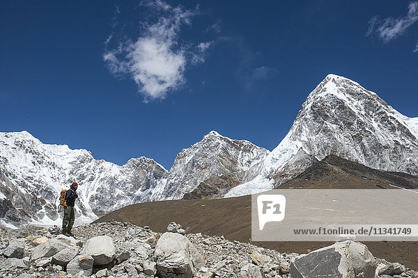 A trekker in the Everest region on the way up to Everest Base Camp  a view of Pumori in the distance  Khumbu Region  Himalayas  Nepal  Asia