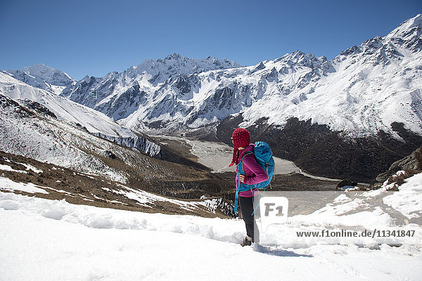 A girl surveys the Langtang valley from the top of Kyanjin Ri with the peak of Ganchempo far in the distance  Langtang Valley  Himalayas  Nepal  Asia