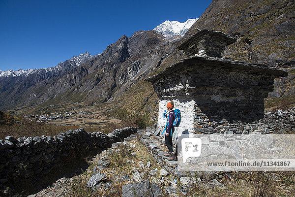 A woman trekking in the Langtang valley rests near a chorten  Langtang Region  Himalayas  Nepal  Asia