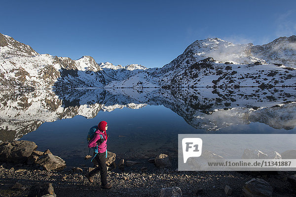 A woman walks past the holy lake of Gosainkund in the Langtang region  Himalayas  Nepal  Asia