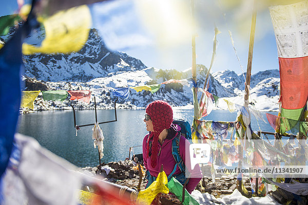 A trekker stands among prayer flags beside the holy lakes at Gosainkund in the Langtang region  Himalayas  Nepal  Asia