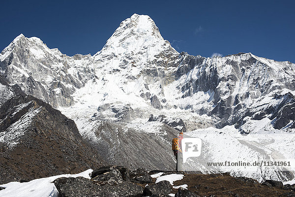 A trekker stops to admire the views of Ama Dablam in the Everest region  Khumbu Region  Himalayas  Nepal  Asia