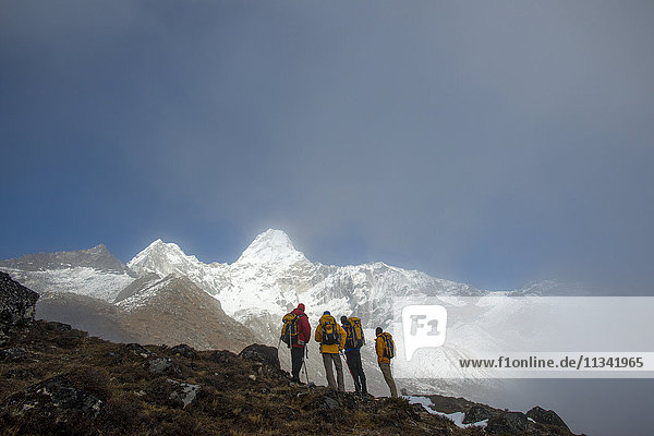 A team of four climbers make their way to Ama Dablam Base Camp  the 6856m peak seen in the distance  Khumbu Region  Himalayas  Nepal  Asia