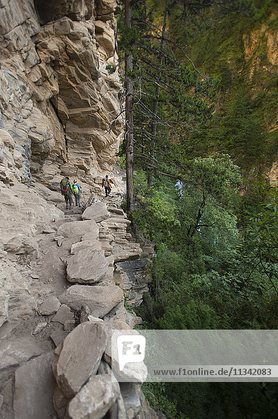 A trekking group makes their way into Dolpa beside the Suli Gadd between Chhepka and Amchi Hospital  Nepal  Asia