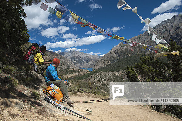 Prayer flags mark a high point in the trail where trekkers are rewarded with their first glimpse of Phoksundo Lake  Dolpa Region  Himalayas  Nepal  Asia
