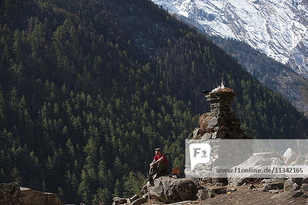 A trekker stops by a chorten in the Tsum Valley  Nepal  Asia