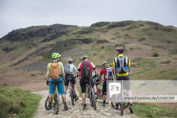 Mountain bikers stop to consider their route around Loughrigg Fell in the Lake District National Park  Cumbria  England  United Kingdom  Europe