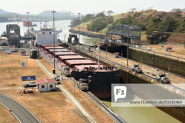 Electric mules guiding Panamax ship through Miraflores Locks on the Panama Canal  Panama  Central America