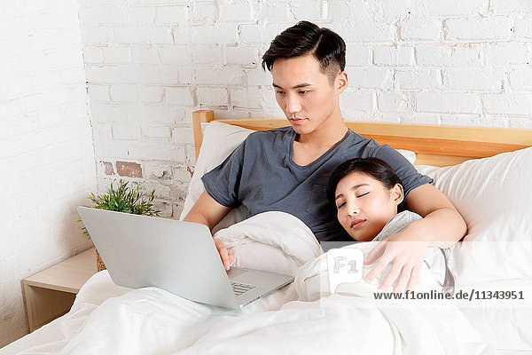 Young couple sitting on the bed to see the computer