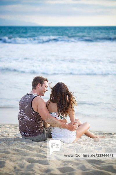 Back side of young couple in their 20s sitting at the beach.