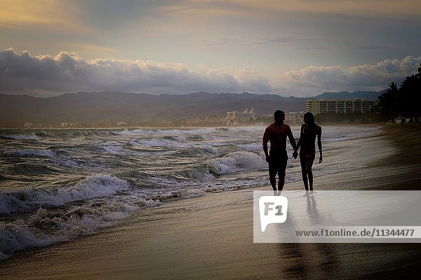 Silhouette of man and woman wlaking hand in hand at a beach at Riviera Nayarit  Mexico.