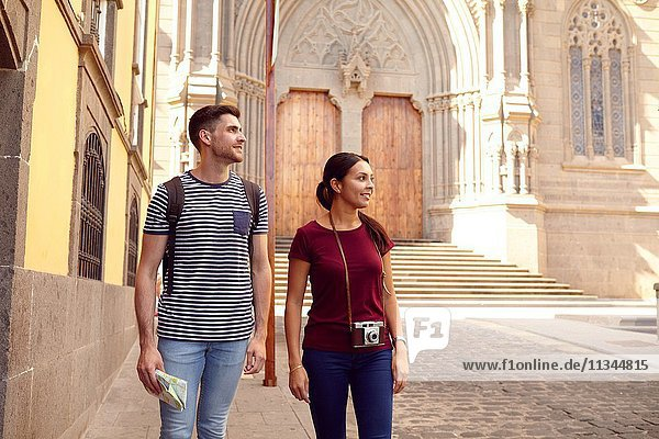 Young tourist couple on vacation with a backpack and map looking sideways while walking dressed casually in jeans and t-shirts with a cathedral behind them.