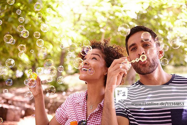 Two young friends joyfully blowing bubbles and smiling in the dappled afternoon sunshine with some trees around them wearing casual clothing.