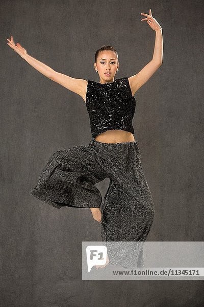 Attractive young woman dancing full length  in black top and baggy gray pants in studio shot on gray background.