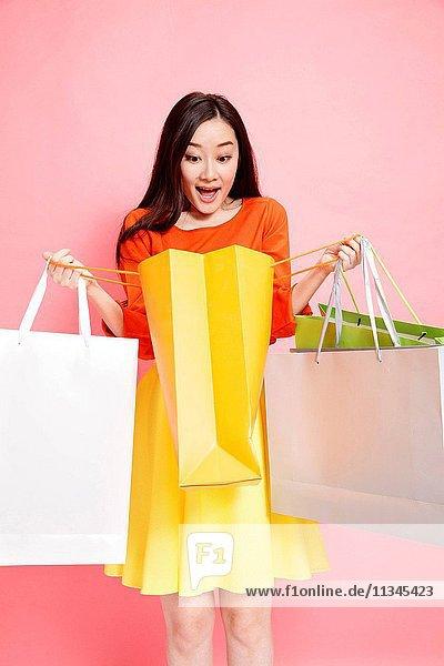 Fashionable young women holding shopping bags